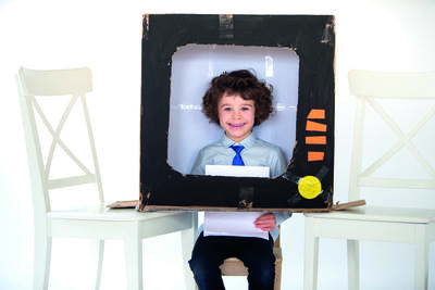 Little boy playing in a cardboard box made to look like a television.